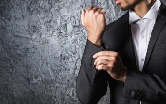 Man in beautiful suit buttoning cuff sleeve